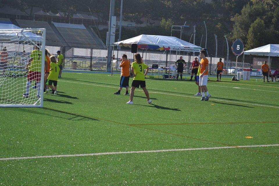Nadia Comaneci (numarul 3), impreuna cu fiul sau Dylan (numarul 1), pe terenul de fotbal la Special Olympics Unified Sports